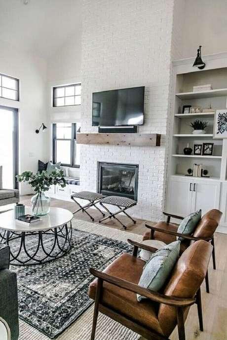 26. Decoração de sala com lareira simples e poltronas de madeira – Foto: Monarch Plank