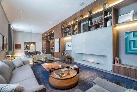 10. Decoração moderna para sala grande com lareira a gás e estante de madeira planejada – Foto: Anexo Arquitetura