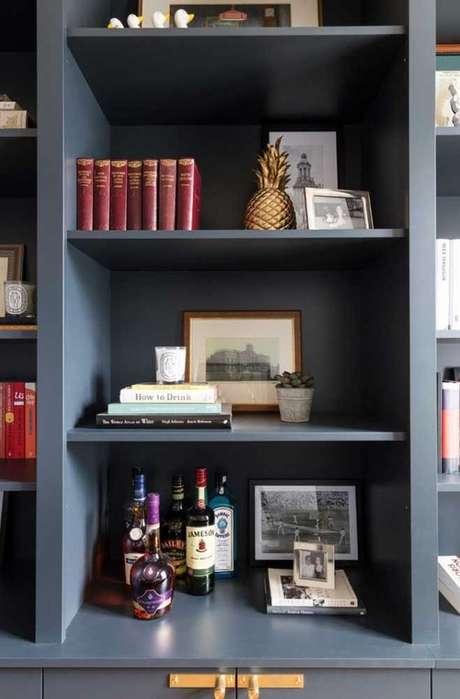 37. Enfeites para estante variados com bebidas livros e fotos – Foto Pinterest