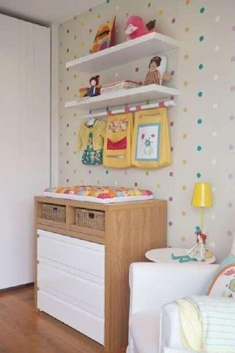 43. Cômoda com trocador de madeira para decoração de quarto de bebê com papel de parede de bolinhas coloridas – Foto: Pinterest
