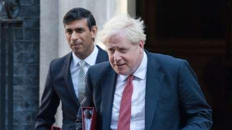 Ministro das finanças Rishi Sunak e primeiro-ministro Boris Johnson (à direita) estão se isolando depois que ambos entraram em contato com ministro da Saúde, cujo teste deu positivo para coronavírus