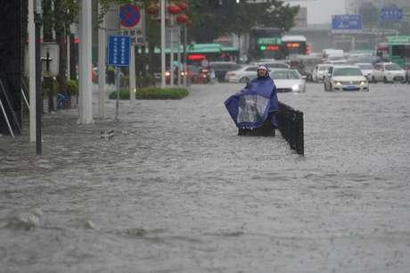 Morador com capa de chuva caminha por rua inundada em Zhengzhou, na província chinesa de Henan 20/07/2021 cnsphoto via REUTERS