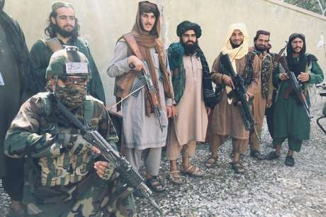 Membro das forças especiais do Talebã posa, ajoelhado, com outros integrantes do grupo