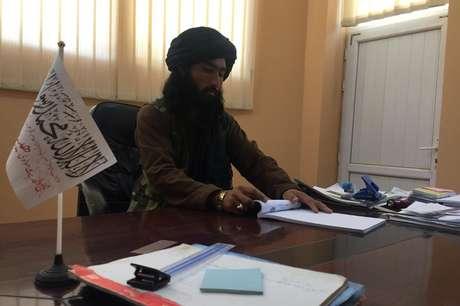"""Prefeito do Talebã em Bactro em sua mesa de madeira, com uma pequena bandeira branca do """"Emirado Islâmico do Afeganistão"""""""