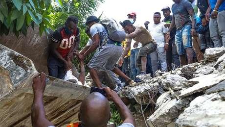 Homens tentam resgatar um sobrevivente debaixo de destroços