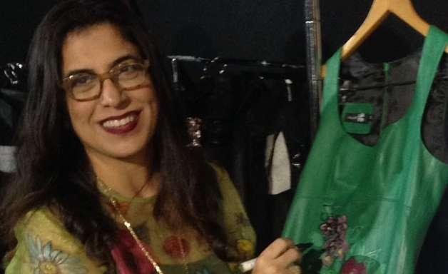 Artista finaliza peças momentos antes de desfile no Fashion Rio