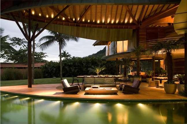 Vista da sala de estar, que é uma espécie de varanda, já que é toda aberta para a entrada da brisa do mar, que refrigera a casa naturalmente. Há uma área reservada às refeições com uma mesa de 14 lugares.