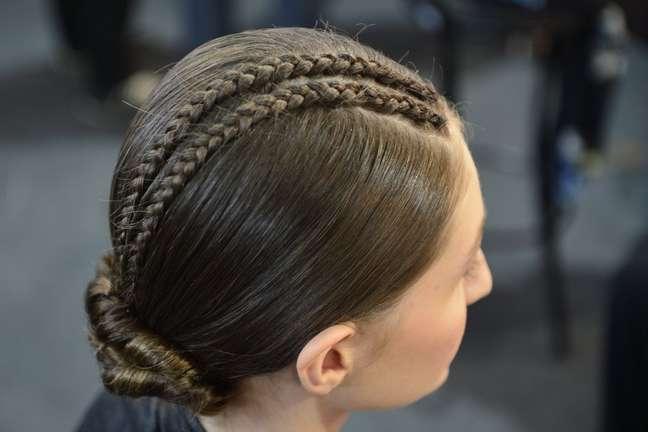 A Acquastudio fez duas pequenas tranças embutidas marcando a risca lateral dos cabelos das modelos, que foram finalizados em um coque torcido