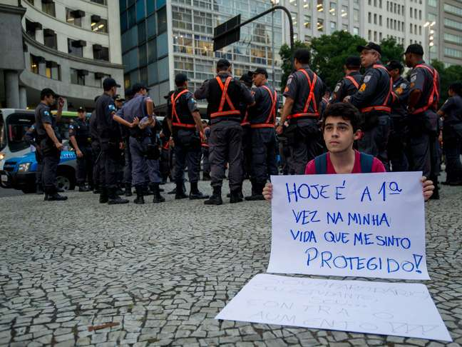 Com cartaz irônico, manifestante cita reforço policial em novo protesto contra reajuste do ônibus no Rio