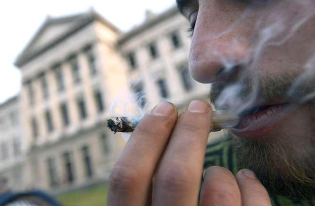 <p>Homem fuma maconha do lado de fora do Congresso uruguaio, onde o projeto foi votado na última quarta-feira</p>