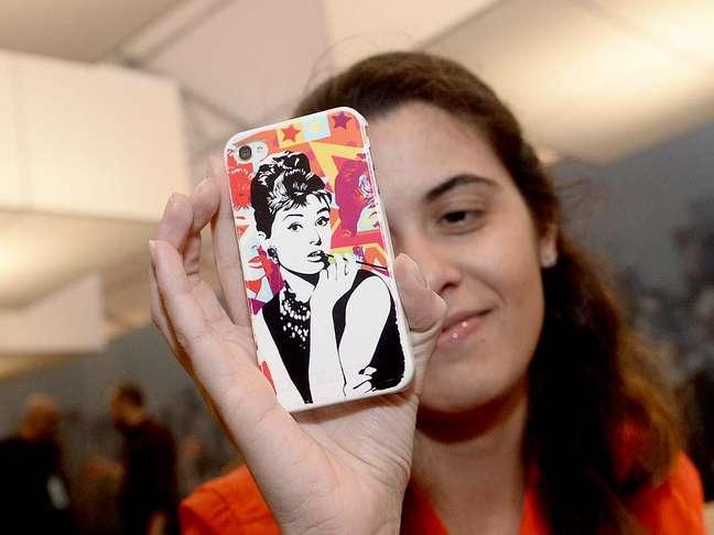<p>A capa para celular traz uma releitura da atriz Audrey Hepburn no filme <em>Bonequinha de Luxo,</em> com fundo colorido, em tons de rosa, amarelo e laranja</p>