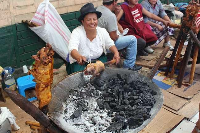<p>Mercado de Gualaceo é movimentado aos domingos; comerciante prepara cuye no carvão</p>