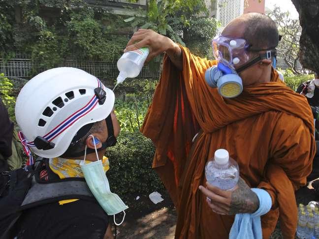 <p><strong>2 de dezembro -</strong> Monge budista ajuda manifestante a limpar seus olhos com solução de água salgada após a polícia disparar bombas de gás lacrimogêneo, em Bangcoc. Milhares de pessoas voltaram às ruas nesta segunda-feira para protestar contra o governo da Tailândia</p>