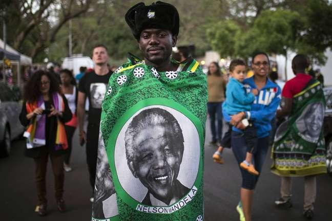 <p>Homem cobre-se com umabandeiracom o rosto de Nelson Mandela</p>