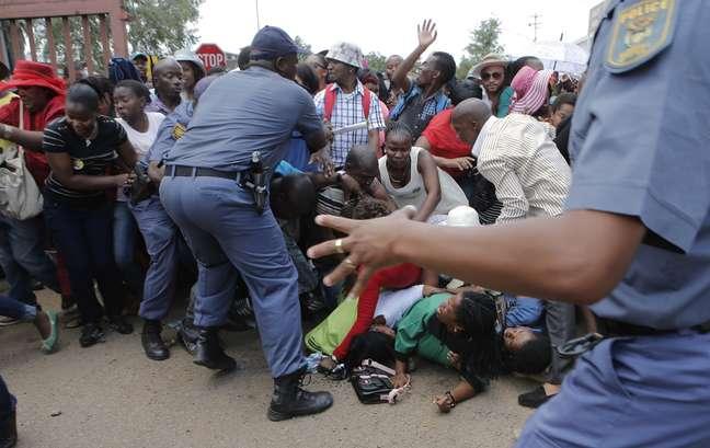 Polícia tenta conter a multidão que se empurra para chegar ao local onde o corpo de Mandela é velado