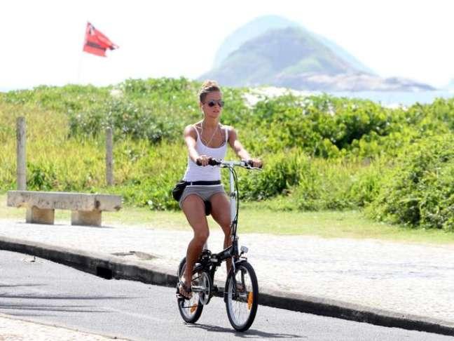 <p>Fernanda Freitas anda de bicileta na orla da praia</p>
