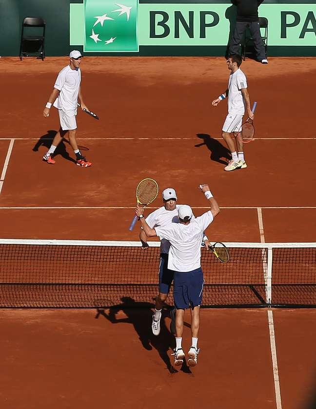 <p>Irm&atilde;os Bob e Mike Bryan (embaixo) comemoram vit&oacute;ria na Copa Davis</p>