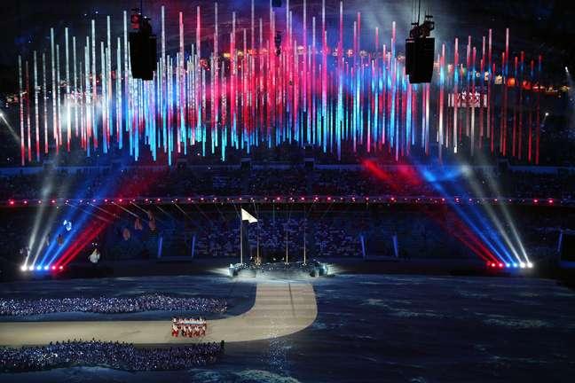 Luzes da russa iluminam estádio na chegada da bandeira nacional ao estádio
