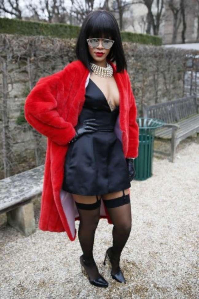 <p>Com look exc&ecirc;ntrico, Rihanna conferiu o desfile de Christian Dior nesta sexta-feira (28), durante a semana de moda de Paris. Casaco de pele vermelho, vestido curto e decotado, meias pretas 7/8 com cinta-liga e escarpins pretos foram as escolhas da cantora</p><p>&nbsp;</p>