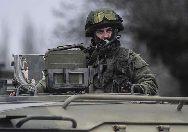 Homem uniformizado olha de cima de um veículo militar enquanto tropas tomam o controle dos escritórios da Guarda Costeira em Balaclava, periferia de Sevastopol, Ucrânia, neste sábado