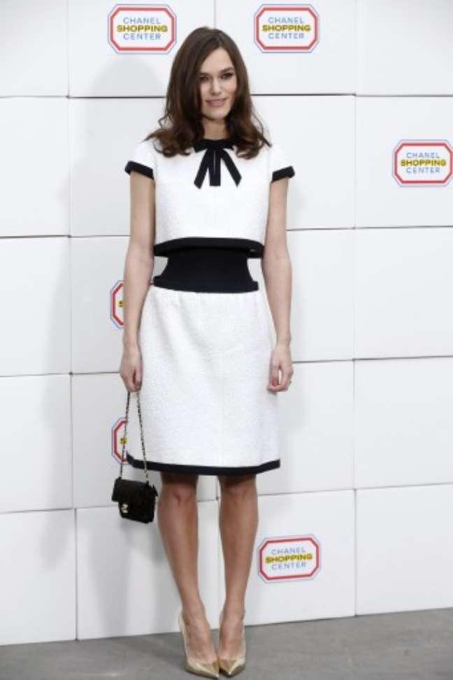 <p>Keira Knightley também conferiu o desfile da Chanel e usou look desenhado por Karl Lagerfeld. O modelo preto e branco, que simulava conjunto detop cropped e saia, evidenciou a cintura já fina da atriz. Escarpins dourados completaram o look</p>