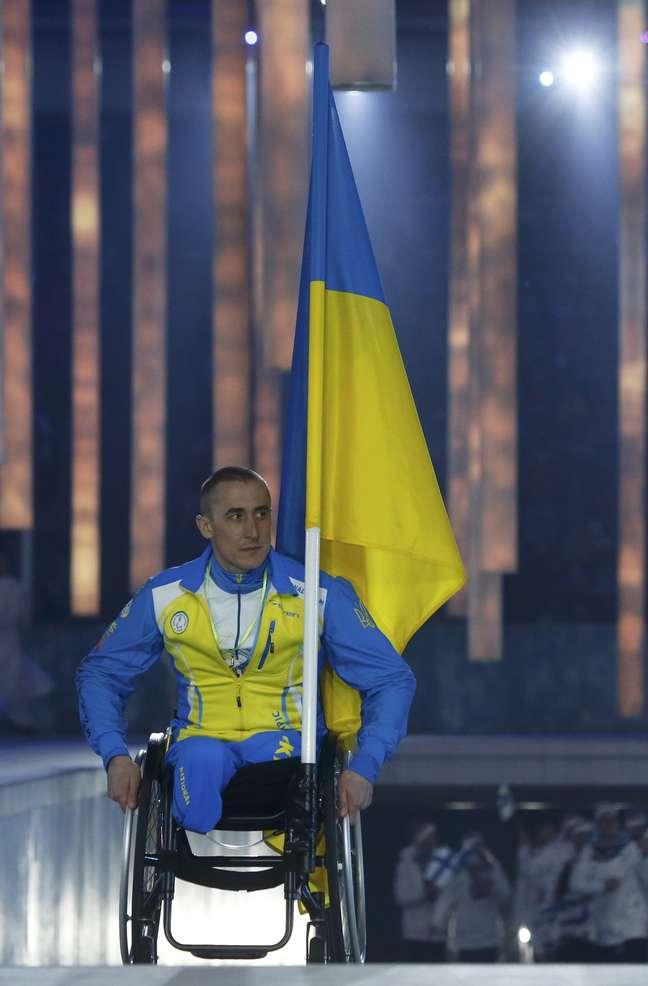 Mykhaylo Tkachenko carrega a bandeira da Ucrânia na cerimônia de abertura
