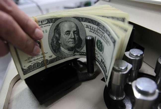 Um funcionário de um banco conta notas de cem dólares em Bangcoc. O Brasil registrou déficit recorde em transações correntes para meses de fevereiro, com o rombo não sendo financiado pelos investimentos estrangeiros diretos no país reforçando o quadro de piora das contas externas do país. 12/10/2010