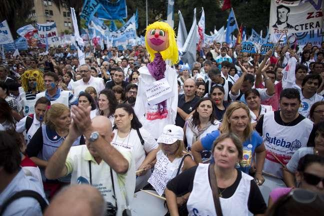 """<p>Um boneco representando um professor com a mensageml: """"Em favor da educação pública"""", se destaca em uma multidão de centenas de professores durante uma manifestação em frente ao Ministério da Educação, em Buenos Aires, Argentina, na quarta-feira, 26 de março</p>"""