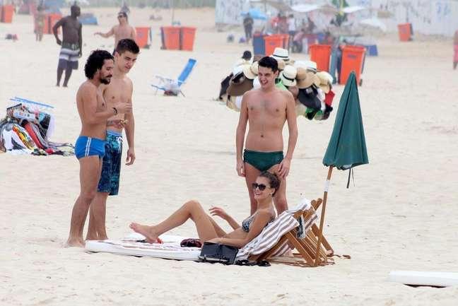 A modelo Carol Francischini, que desfilou nesta terça-feira (8) para a grife Patrícia Viera no Fashion Rio, curtiu praia em Ipanema nesta quarta-feira (9) ao lado de três homens