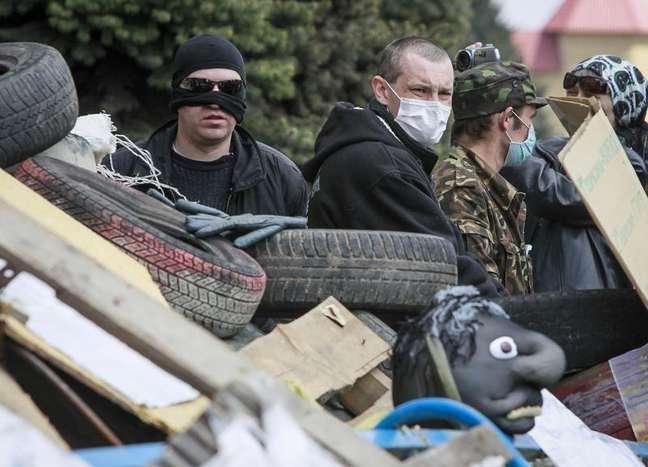 Manifestantes pró-Rússia com máscaras guardam uma barricada na frente do escritório do serviço de segurança SBU, tomado por eles, em Luhansk, no leste da Ucrânia. Habitantes russófonos do leste da Ucrânia mentiram ao se dizerem sob ataque, na tentativa de justificar um envolvimento da Rússia na atual crise, disse um relatório de direitos humanos da ONU divulgado na terça-feira. 15/04/2014
