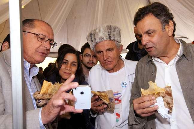 <p>Geraldo Alckmin (esq), opadre Rosalvino Morán (centro) e Aécio Neves comem pastel na Feira Tecnológica</p>