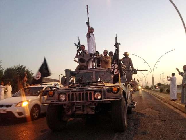 <p>Extremistas do&nbsp;grupo Estado Isl&acirc;mico desfilam&nbsp;em&nbsp;um&nbsp;ve&iacute;culo tomado das for&ccedil;as de seguran&ccedil;a iraquianas em uma avenida da cidade de Mossul, em 23 de junho</p>