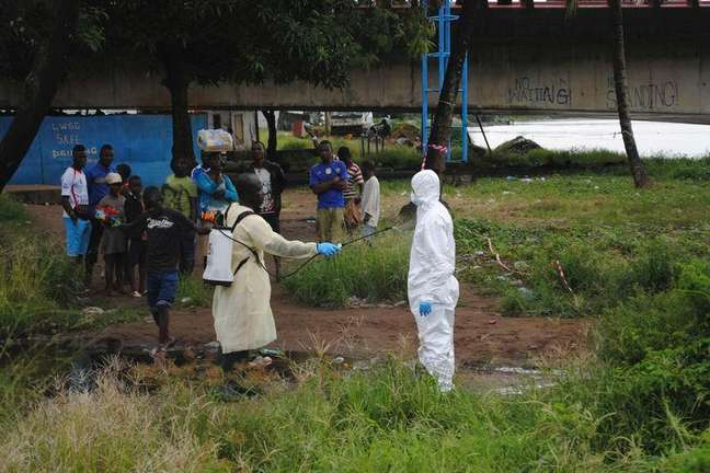 <p>Agente da saúde com vestimenta especial é desinfetado após lidar com um corpo infectado com ebola, em Monróvia, na Libéria</p>