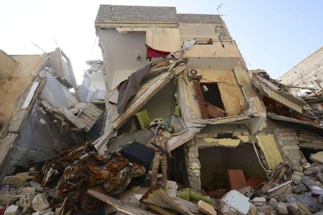 <p>Um membro das for&ccedil;as pr&oacute;-governo da L&iacute;bia&nbsp;segura uma arma pr&oacute;ximo aos escombros de um edif&iacute;cio danificado durante os confrontos com os jihadistas do grupo Ansar al-Sharia, em Benghazi, em 21 de janeiro</p>