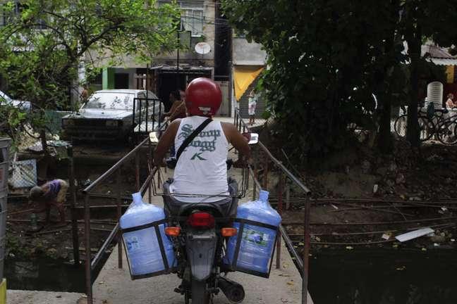 Moradores abastecem galões com água potável de uma bica no canal