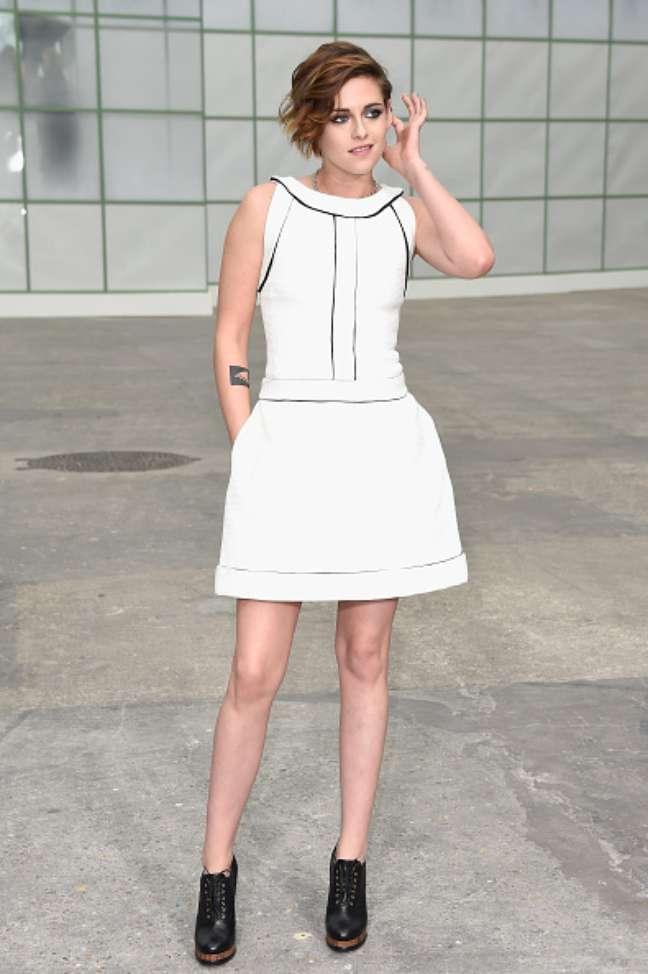 Kristen Stewart escolhe roupa branca, com saia curta, e debruns pretos para assistir ao desfile da Chanel, em Paris