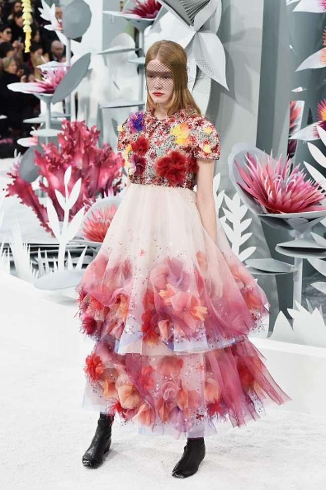 Flores de papel do cenário se misturam a flores aplicadas nos vestidos, como nesse look também usado com bota baixa
