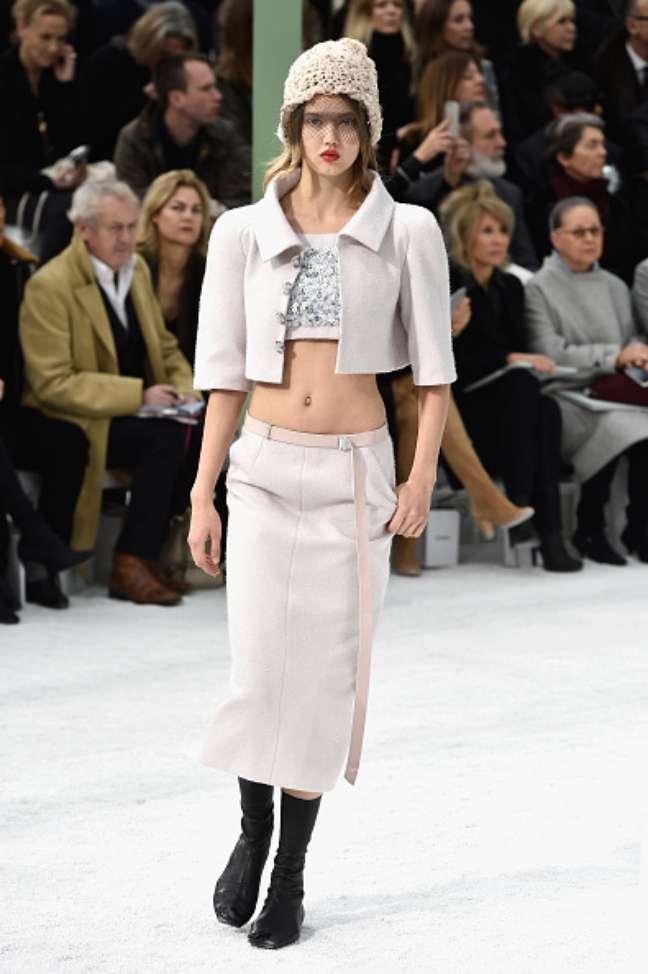 A modelo Lindsey Wixson, conhecida pela sua boca em forma de coração, foi uma das modelos do desfile: saia reta mídi, top e casquinho curto se complementam com gorro e bota