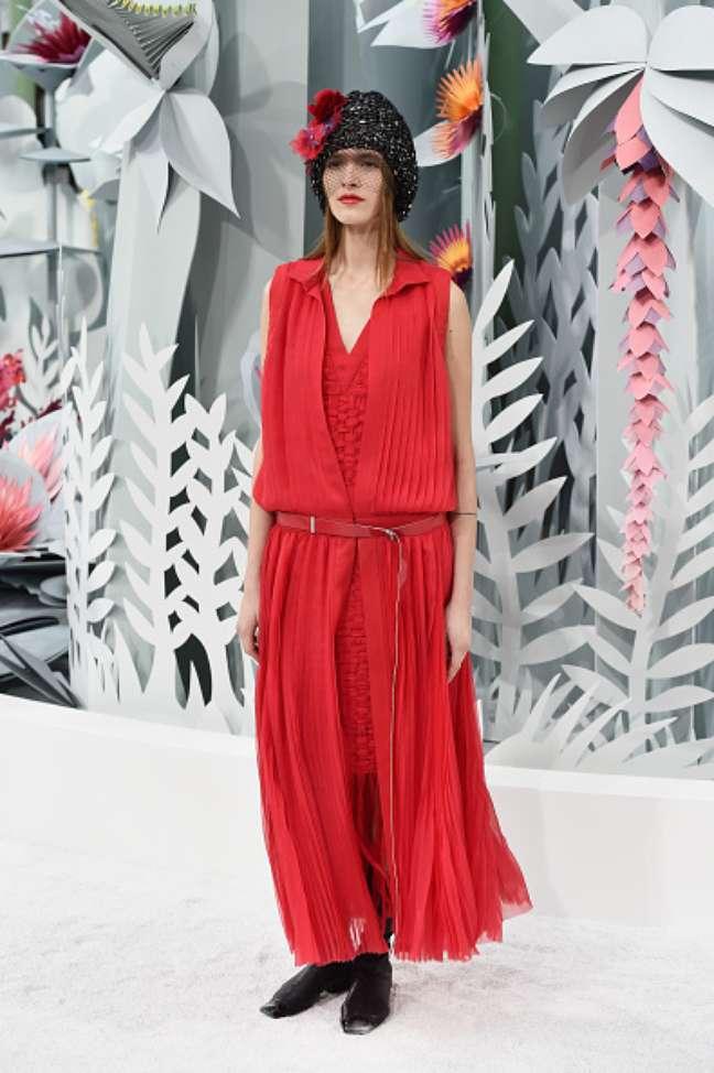 Vestido vermelho comprido, com leve perfume anos 20, surge com gorro enfeitado com flores