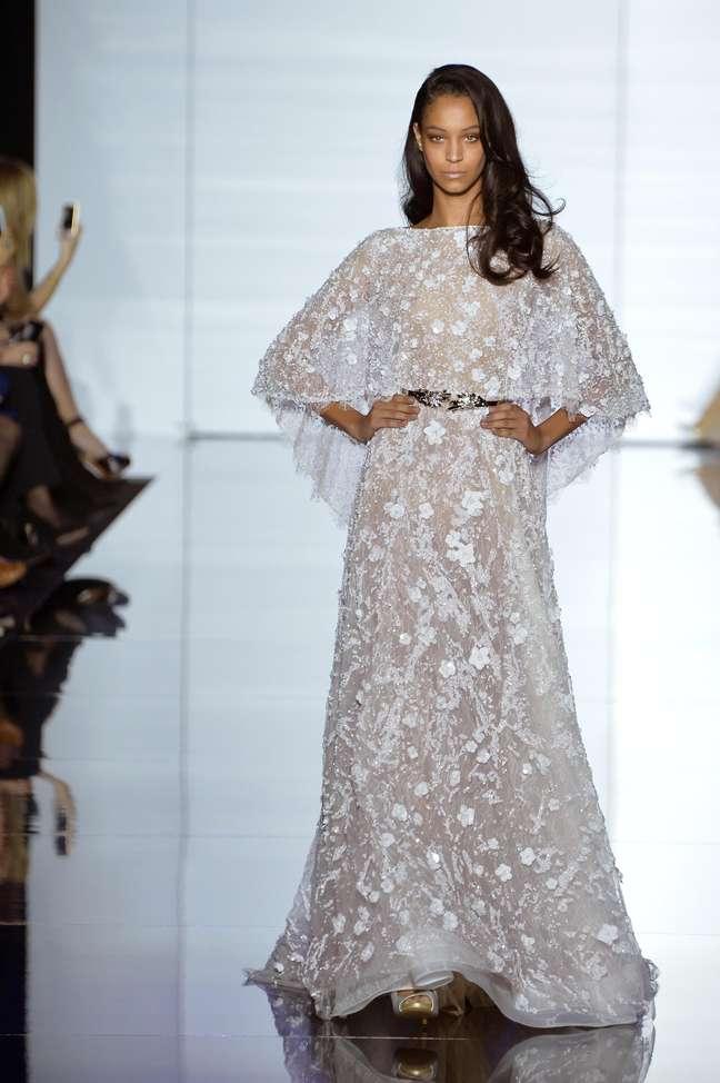 Com estilo que remete aos anos 70, forte tendência nas passarelas, o vestido de Zuhair Murad traz capa pelerine no lugar de véu e sai sem tanto volume