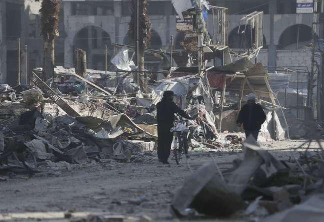 <p>Homens caminham na cidaderebelde deDouma, próxima aDamasco, danificadapelos bombardeios do regime de Bashar al Assad</p>
