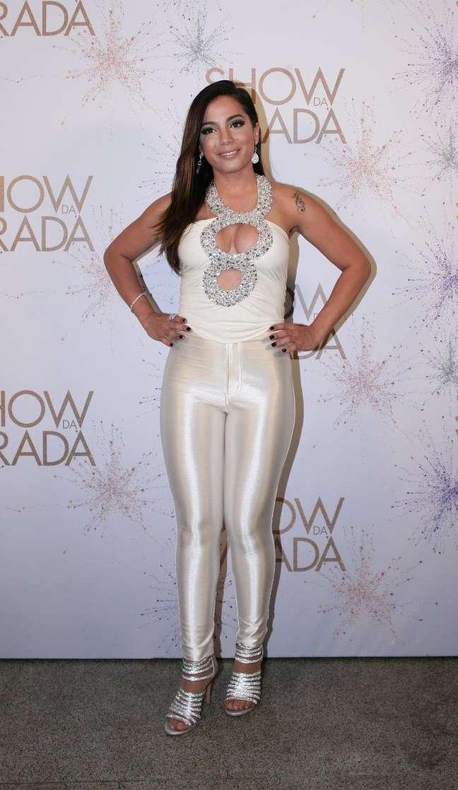 Para o show da virada, escolheu um body que não valoriza os seios, apesar do decote, pois ficam espremidos. E para completar, calça justa branca e com brilho. Look sem graça e nada sofisticado.