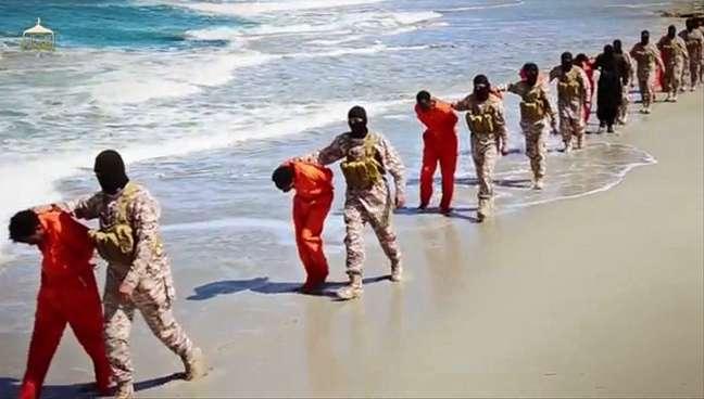 Homens vestidos com roupas laranja são levados para uma praia para serem executados por membros do Estado Islâmico