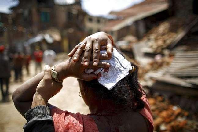 Mulher ferida em terremoto caminha para hospital em Sankhu, no Nepal. 12/05/2015