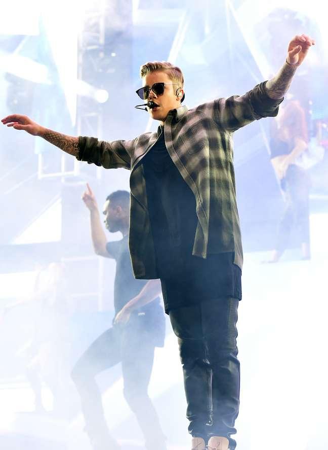 Em outra parte do show, Justin Bieber acrescenta camisa xadrez à sobreposição das camisetas