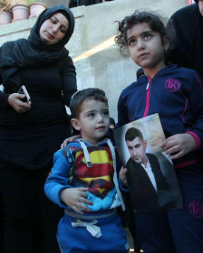 Ali (à esq.) e Malak (dir.) levam a fotografia de Adel Termos durante funeral do pai