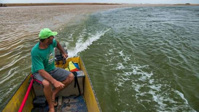 Em Regência, pescador observa o encontro da lama com a água do rio, já chegando ao mar