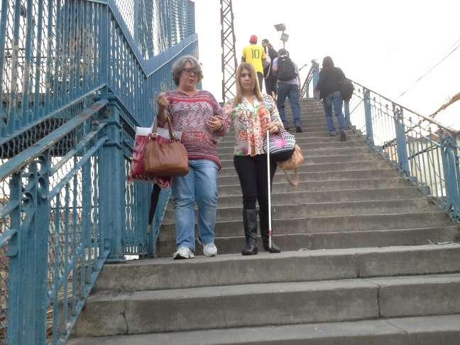 Portadora de deficiência visual, Sandra R. Lima tem de contar com a ajuda de amigas para subir e descer as escadas da estação de trem do Riachuelo – entre Maracanã e Engenho de Dentro. É o seu caminho diário para o trabalho.