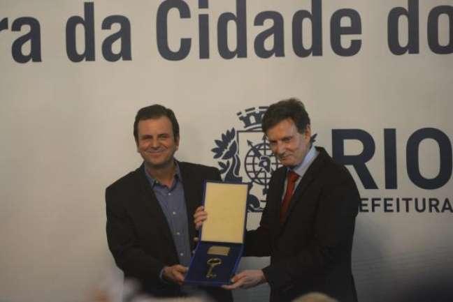 O prefeito Marcelo Crivella recebe o cargo do ex-prefeito Eduardo Paes; cenário vai se inverter em 2021