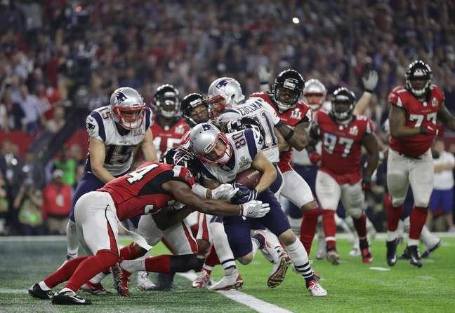O wide-receiver Julian Eldeman atropela a defesa do Falcons para anotar um touchdown a favor do Patriots